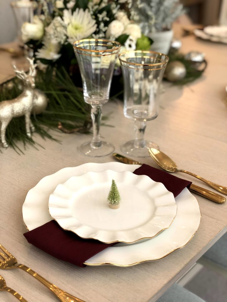 Holiday Table Settings with lots of texture, white ruffle plates, and sparkly reindeer.